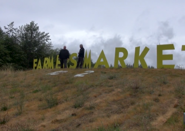 Cook and the Comic at Bayview Farmer's Market sign