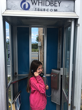 little girl using free community Whidbey Telecom phone booth